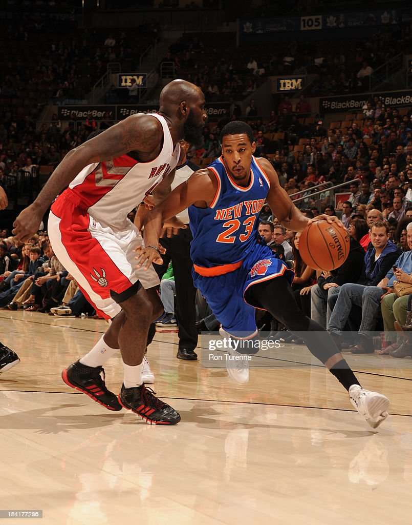 Toure' Murry #23 of the New York Knicks drives to the basket against <a gi-track='captionPersonalityLinkClicked' href=/galleries/search?phrase=Quincy+Acy&family=editorial&specificpeople=5674079 ng-click='$event.stopPropagation()'>Quincy Acy</a> #4 of the Toronto Raptors during the game on October 11, 2013 at the Air Canada Centre in Toronto, Ontario, Canada.