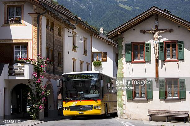 Touring coach passes Christian crucifix on a traditional house in Mustair Switzerlan