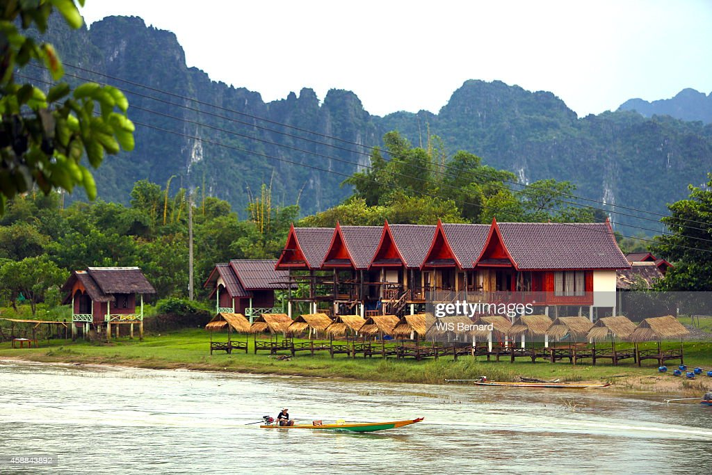 Tourism in Laos in the town of Vang Vieng looking like the Halong bay near the river Nam Song small hotel on the edge of the water respecting Asian...