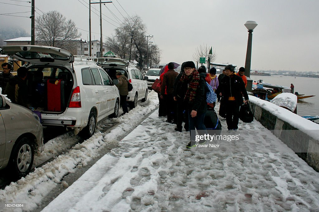 Tourist alight from vehicles to enter houseboats after a snowfall on February 23, 2013 in Srinagar, Indian Administered Kashmir, India. Several parts of the Kashmir Valley, including the summer capital Srinagar, experienced fresh snowfall today, prompting the authorities to issue an avalanche warning and leading to closure of the Jammu-Srinagar Highway, the only road link between Kashmir and rest of India.