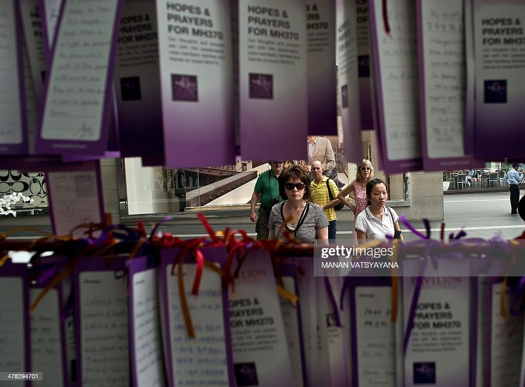 Tourist and office workers read messages expressing prayers and well-wishes for passengers onboard missing Malaysia Airlines (MAS) flight MH370, displayed outside a mall in Kuala Lumpur on March 13, 2014. Malaysia said on March 13 it dispatched an aircraft to investigate the site where Chinese satellites photographed three 'suspected floating objects', near an area where several nations have been hunting for wreckage from the missing passenger plane.