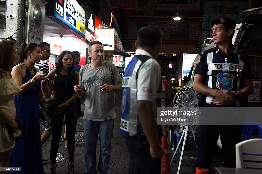 A tourist asks to take a picture with a member of the FTPA on Pattaya's Walking Street on July 31, 2014 in Pattaya, Thailand. Since 2002, members of the Foreign Tourist Police Assistants (FTPA) of Pattaya have been assisting local police on Walking Street, Pattaya's main nightlife area. Members of the FTPA carry handcuffs, batons, and pepper spray, and are charged primarily with assisting foreign visitors and the Thai police, as well as breaking up fights and catching thieves.