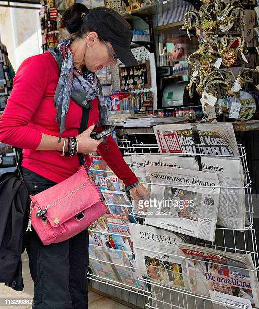 A tourist at a newsagent looks at a newspapers that display pictures of the Royal Highnesses Prince William Duke of Cambridge and Catherine Duchess...