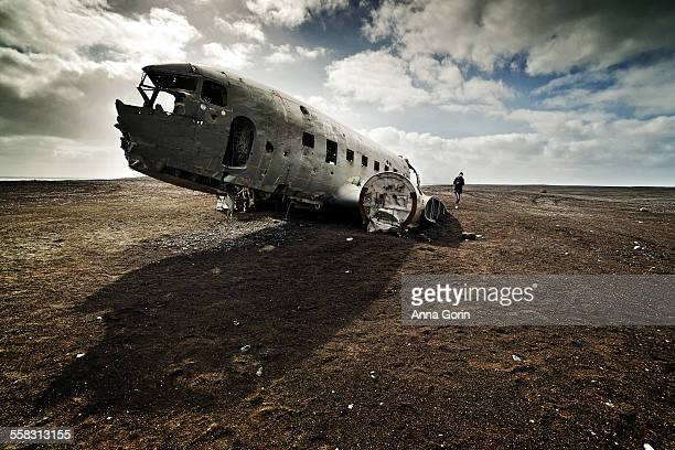 Tourist at plane wreck on black sand beach Iceland