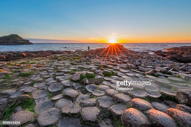 Tourist at Sunset over Giants Causeway, Northern Ireland