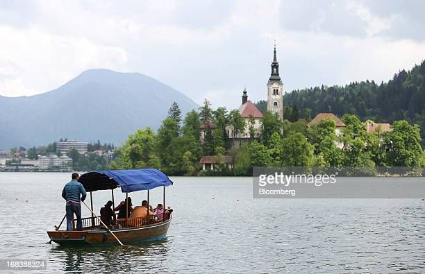 A tourist boat makes its way towards the church of the Assumption of Mary a pilgrimage site and tourist attraction on Lake Bled Slovenia on Wednesday...