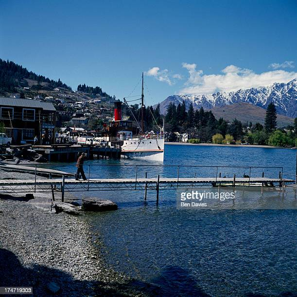 A tourist boat on beautiful Lake Wakatipu framed by snowy mountain peaks and fjords at Queenstown on New Zealand's South Island A major tourist...