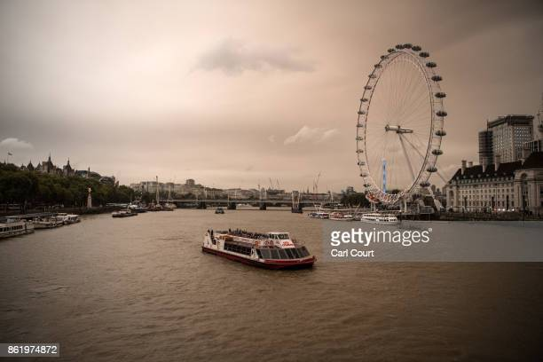 A tourist boat passes near the London Eye during a reddish sky caused by remnants of Hurricane Ophelia dragging in dust from the Sahara Desert on...