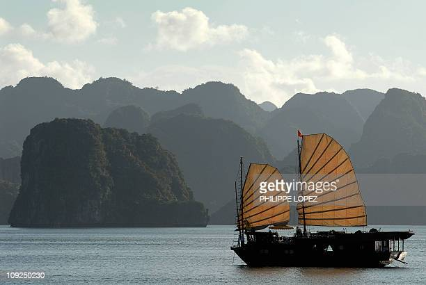 A tourist boat sails past the stone islands of Halong Bay 08 July 2007 Vietnam received more than 2 million foreign visitors in the first half of...