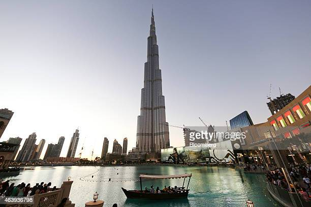 A tourist boat sits in the lagoon outside the Dubai Mall during an evening light show at the Burj Khalifa tower center in Dubai United Arab Emirates...