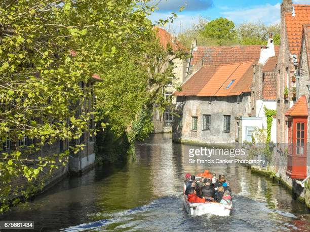 Tourist boat with unrecognizable tourists along the picturesque canals of Bruges, Flanders