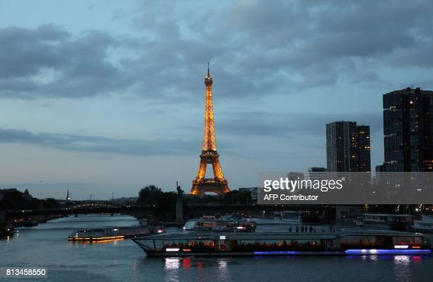 Tourist boats cruise on the Seine River near the Statue of Liberty replica and the Eiffel Tower at sunset in Paris on July 12 2017 / AFP PHOTO /...