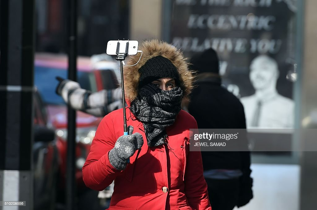 A tourist braves the cold morning to explore downtown Manhattan in New York, on February 14, 2016. / AFP / Jewel Samad