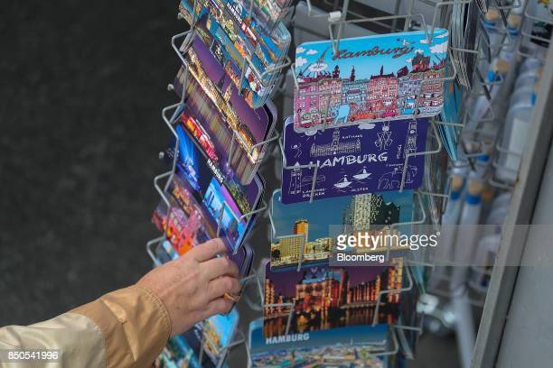 A tourist browses postcards outside a gift shop in Hamburg Germany on Wednesday Sept 20 2017 Germany's Bundesbank said last month that industrial...
