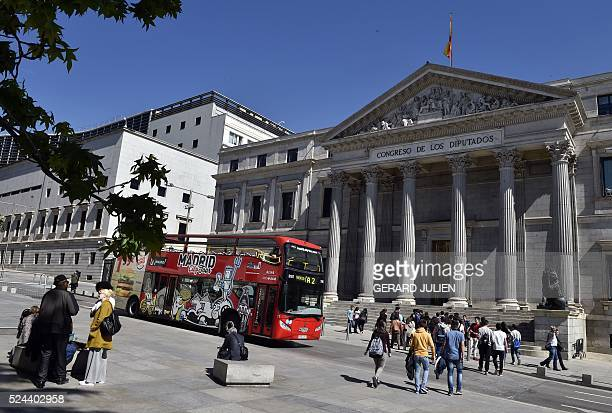 A tourist bus and people pass in front of Spanish parliament in Madrid on April 26 2016 Spanish parties restarted coalition negotiations on Tuesday...