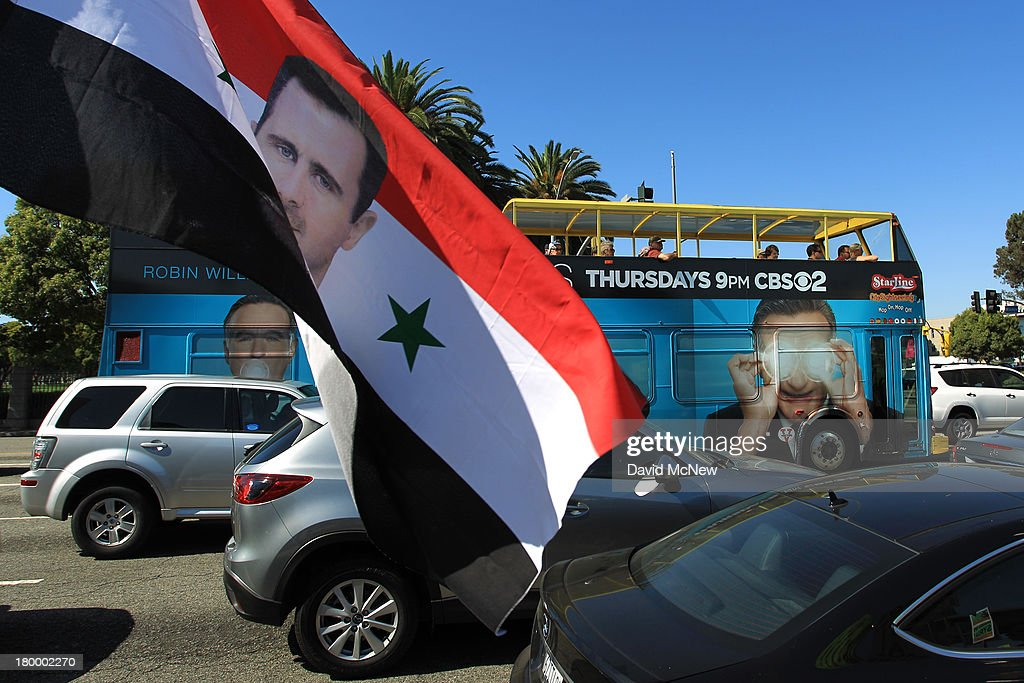 A tourist bus passes a flag held by a protester bearing a picture of Syrian president Bashar Hafez al-Assad at a rally to urge Congress to vote against a limited military strike against the Syrian military in response to allegations that Assad has used sarin gas to kill civilians on September 7, 2013 in Los Angeles, California. The Obama administration claims to have clear evidence that the Syrian military broke international law by killing nearly 1,500 Syrian civilians, including at least 426 children, in a chemical weapons attack on August 21, and is seeking the support of Congress for a missile strikes to prevent future chemical weapons attacks by the regime and other nations.