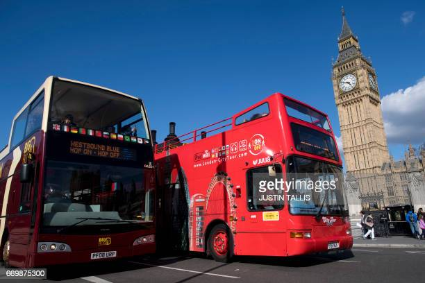 Tourist busses pass the Elizabeth Tower commonly referred to as Big Ben in Westminster central London on April 18 2017 British Prime Minister Theresa...
