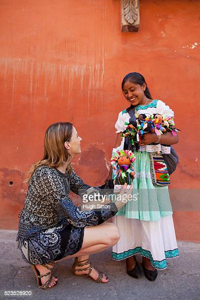 Tourist buying Mexican dolls from saleswoman