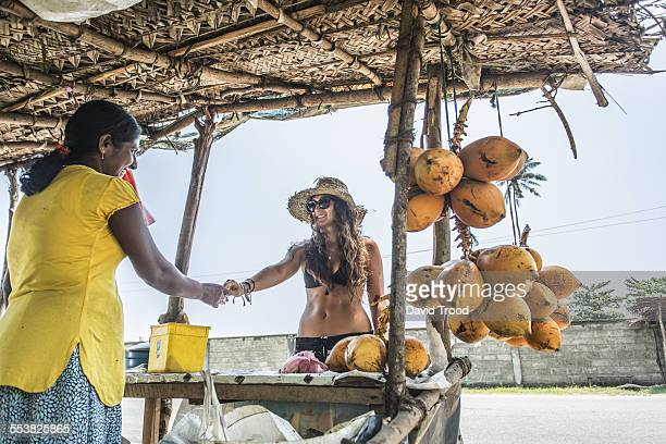 Tourist buying some coconuts at a road market.