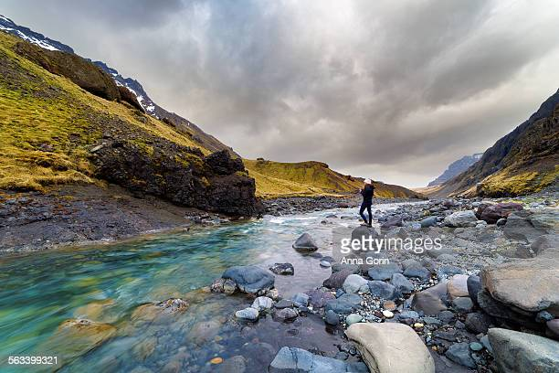 Tourist by stream in southern Iceland, overcast