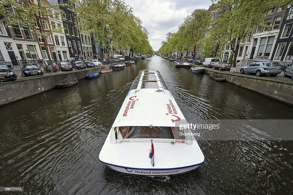 A tourist canal boat in the name of Holland International, operated by the Canal Company B.V., ferries visitors along a canal in the Dutch city of Amsterdam, Netherlands, on Tuesday, May 14, 2013. Euro-area data this week will probably reveal economic scars of the sovereign debt crisis confirming that the region is now suffering the longest recession since the single currency's creation. Photographer: Jock Fistick/Bloomberg via Getty Images