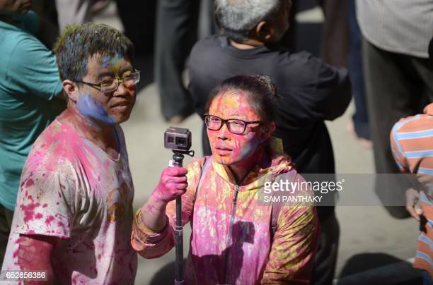 A tourist captures the action on her camera as Indian Hindu devotees are sprayed with coloured water as they celebrate the Holi festival at the...