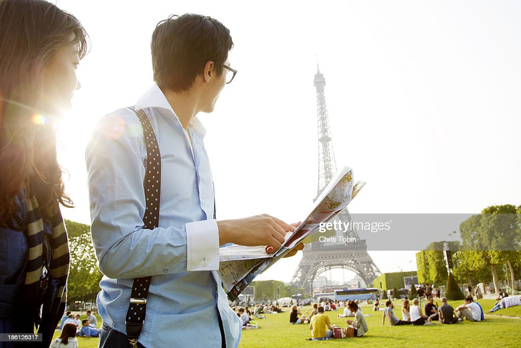 Tourist couple at the Eiffel Tower with map