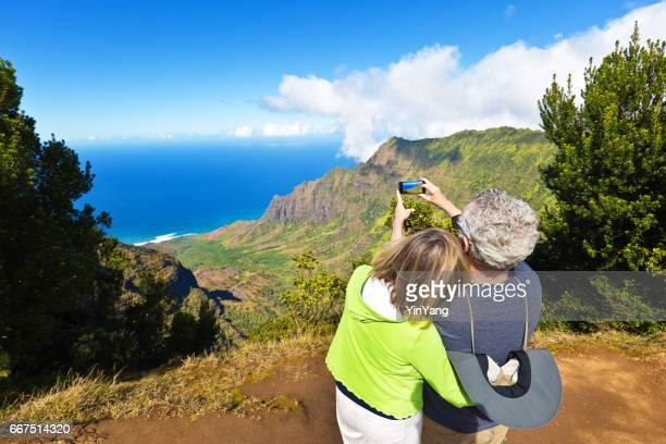 Tourist Couple at Waimea Canyon State Park Kalalau Beach, Kauai, Hawaii