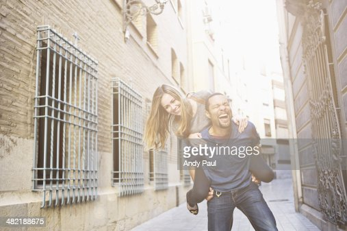 Tourist couple giving piggy back ride, Valencia, Spain