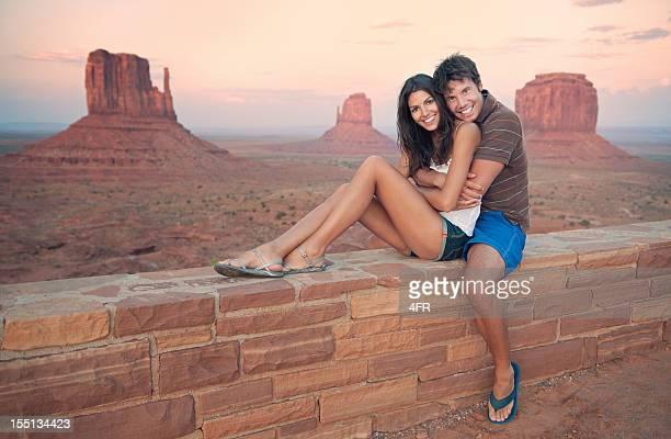 Touristes Couple devant le Monument Valley au coucher du soleil (XXXL