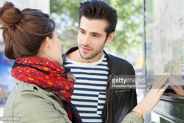 Tourist couple looking at city map discussing sightseeing plan