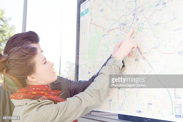 Tourist couple looking at outdoor city map at tourist information station