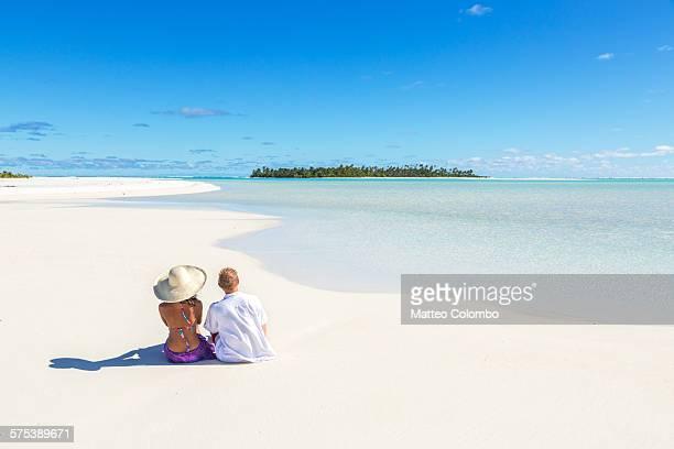 Tourist couple sitting on sandy beach, Aitutaki