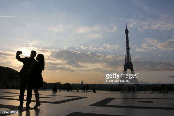 A tourist couple takes a selfie on the Trocadero plaza in front of the Eiffel tower on April 2017 at sunrise in Paris / AFP PHOTO / LUDOVIC MARIN