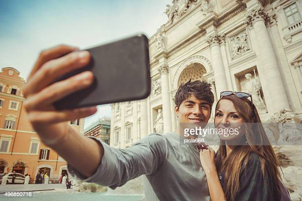 Tourist couple taking a selfie at Trevi fountain