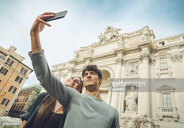 Coppia turistico prendendo un selfie con fontana di Trevi
