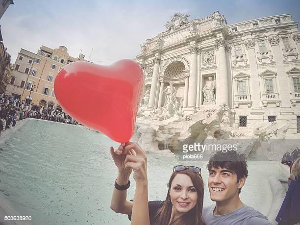 Touristes couple prenant un selfie avec cœur de la fontaine de Trevi