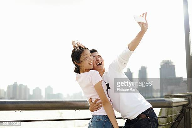 Tourist couple taking smartphone selfie, The Bund, Shanghai, China
