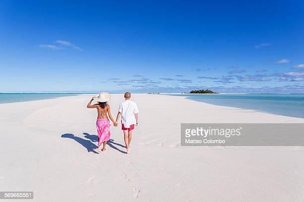Tourist couple walking on deserted tropical island