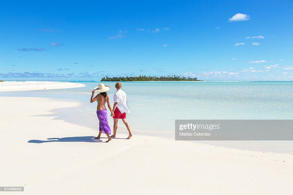 Tourist couple walking on sandy beach, Aitutaki