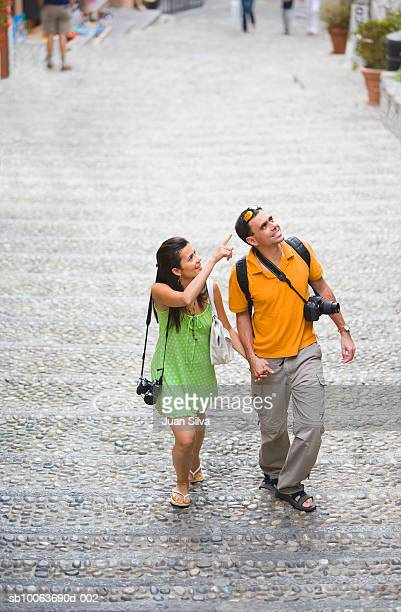 Tourist couple walking with cameras in street, woman pointing, elevated view