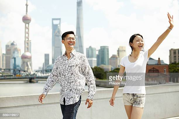 Tourist couple waving, The Bund, Shanghai, China