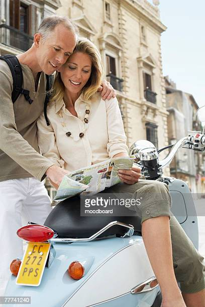 Tourist Couple With Scooter in Square