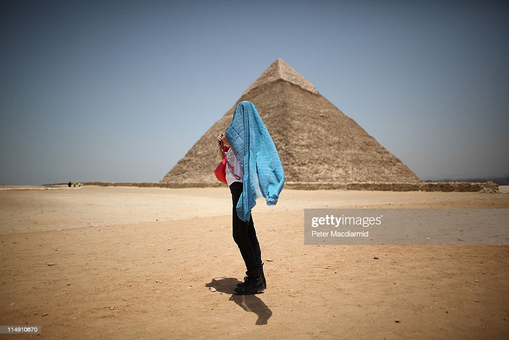 A tourist covers her head against the sun in sight of the Pyramid of Chephren on May 28, 2011 in Giza, Egypt. Protests in January and February brought an end to 30 years of autocratic rule by President Hosni Mubarak who will now face trial. Food prices have doubled and youth unemployment stands at 30%. Tourism is yet to return to pre-uprising levels.