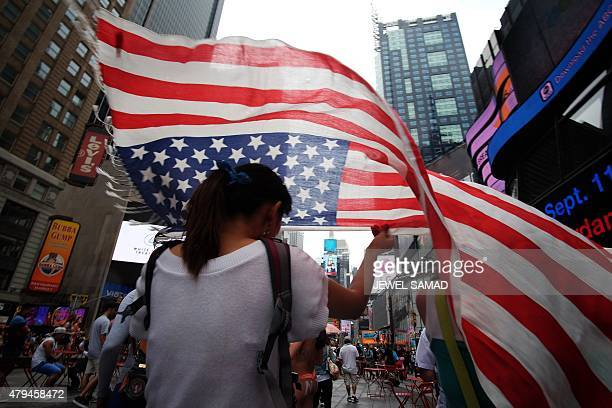A tourist covers her head with a scarf made like a US flag as she walks under light rain in Times Square on July 4 2015 in New York The US is ramping...
