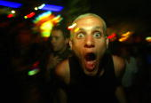 A tourist dances to rave music March 7 2004 in Koh Phangan Thailand at the monthly 'Full Moon' party where thousands of foreigners and Thai citizens...