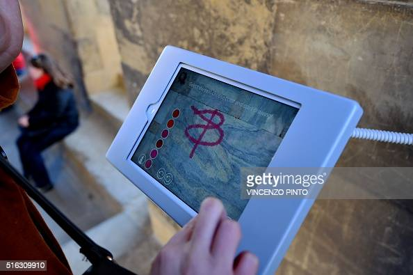 A tourist draws a digital graffiti on a tablet screen choosing between different tools colours and virtual surfaces on March 17 2016 during a visit...