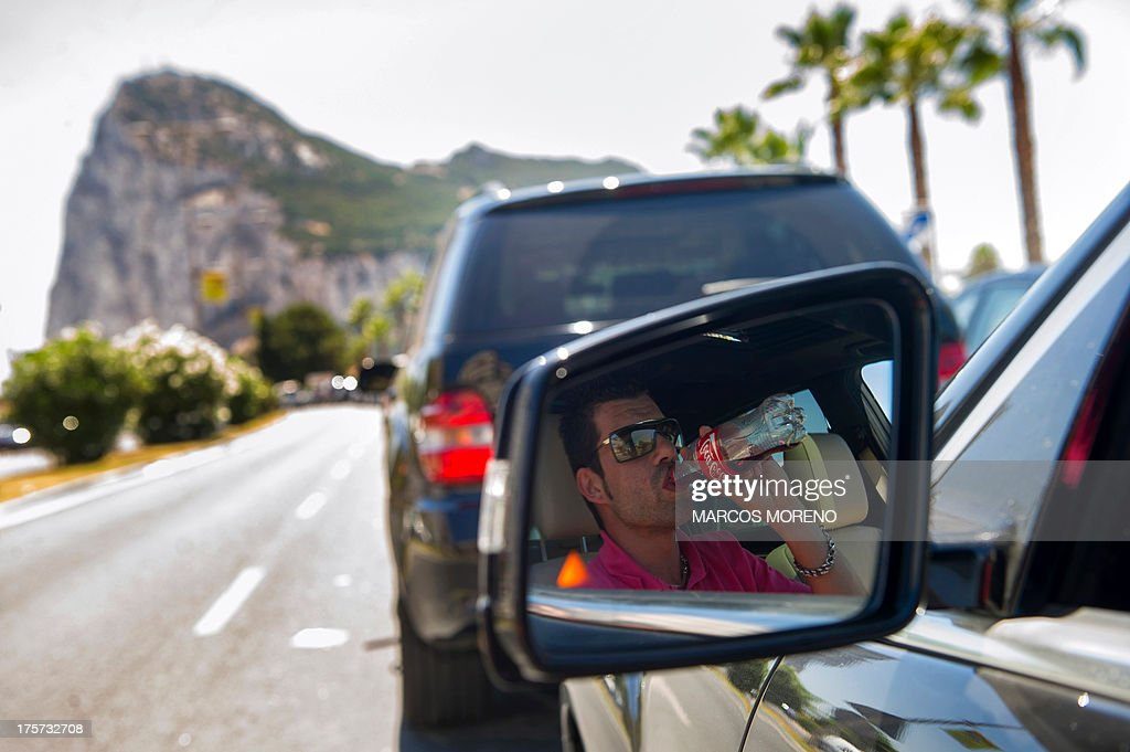 A tourist drinks soda in his car as he queues at the border crossing between Spain and Gibraltar in La Linea de la Concepcion on August 7, 2013. Gibraltar on August 5 blasted a Spanish threat to impose a 50-euro ($66) car toll at the border with the tiny British-held territory as North Korean-style 'sabre rattling'. It was the latest in a string of spats going back decades between Spain and Gibraltar, frequently sparked by disputes over fishing rights around the British outpost that Madrid wants to reclaim as its own.