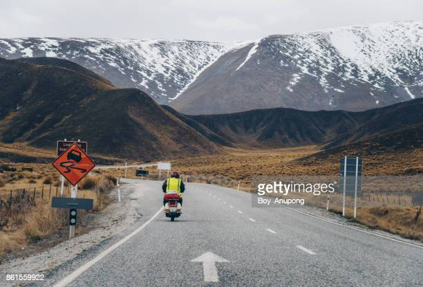 Tourist driving motorcycle on the road of Lindis pass in the South Island of New Zealand.