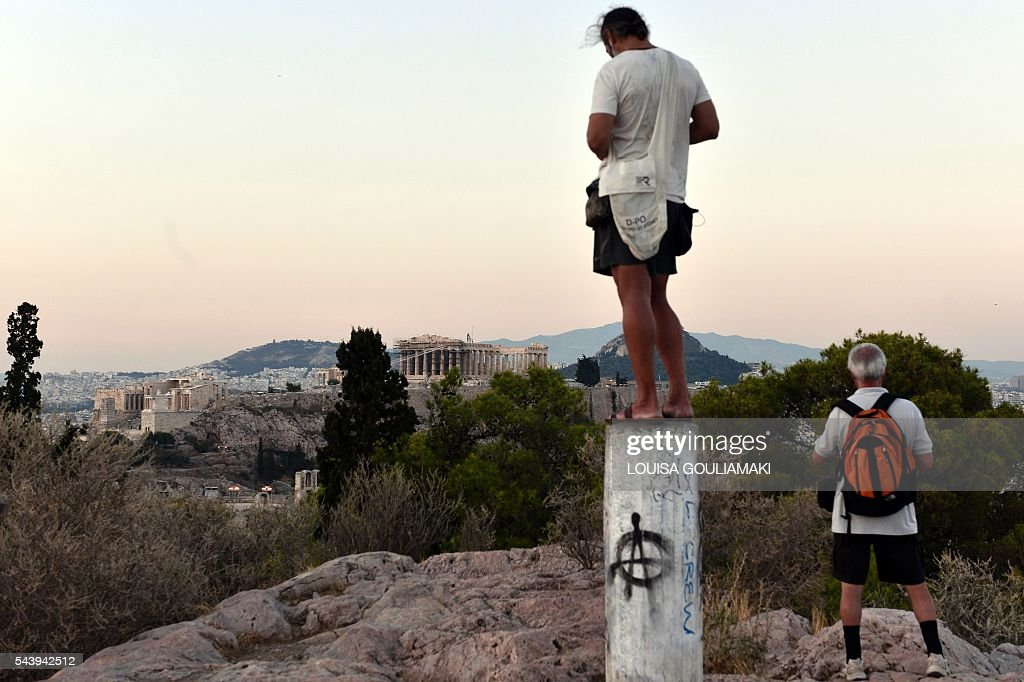Tourist enjoy an evening sightseing view of the Acropolis from Philopappos hill in Athens on June 30, 2016. / AFP / LOUISA